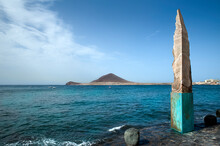 An Obelisk Made Of Volcanic Rock In El Medano, Monument Of Sharp Cut Lava With Molted Rock Visible Through Situated On A Promenade At One End Of The Picturesque Town In Tenerife, Canary Islands, Spain