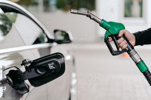 Fotografie, Tablou Cropped shot of mans hand pumping gasoline fuel in car at gas station