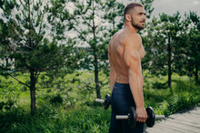 Outdoor Shot Of Muscular Strong Man Prepares For Barbell Workout, Lifts Weight And Poses At Street, Gives Motivation To Everyone. Male Weightlifter Does Biceps Exercises, Wears Sportive Clothes