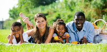 Smiling Young Parents With Happy Preteen Daughter And Son Having Fun Together At Picnic In Summer City Park, Lying On Green Grass..