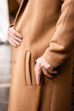 Cropped View Of Aged Man In Autumn Coat Standing With Walking Stick At Underground Station, Blurred Background