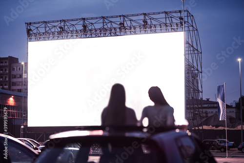 Fotografija Rear view of two female friends sitting in the car while watching a movie in an