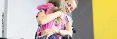 Woman in wheelchair hugs little girl Fototapete