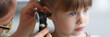 Leinwandbild Motiv Otorhinolaryngologist examines little girl's ear with otoscope. Adenoiditis as cause of otitis media in children concept.