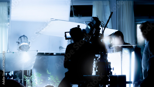 Fotografia, Obraz Silhouette images of video production behind the scenes or b-roll or making of TV commercial movies that film crew team lightman and videos cameraman working together with movie director in studio