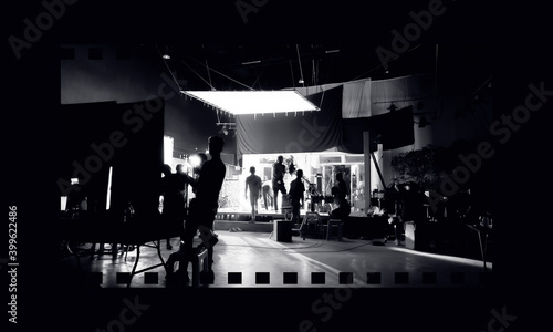 Fényképezés Silhouette images of video production behind the scenes or b-roll or making of TV commercial movies that film crew team lightman and videos cameraman working together with movie director in studio