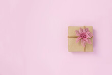 Present Box Made Of Kraft Paper Decorated With Decorative Poinsettia On Pink Background. DIY Gift Concept. Copy Space