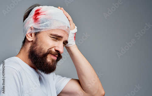 Fotografija man with bandaged head and blood concussion gray background medicine