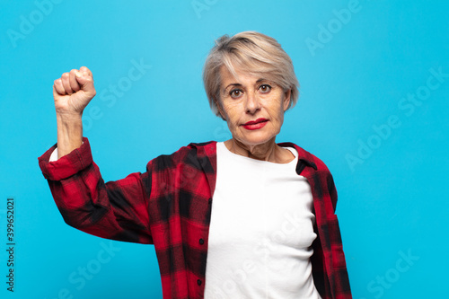 Fototapeta middle age woman feeling serious, strong and rebellious, raising fist up, protes