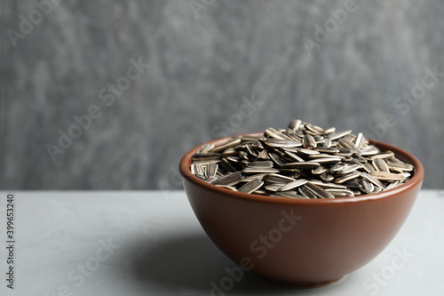 Valokuva Raw sunflower seeds in bowl on grey table. Space for text