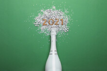 Year Number 2021, Bottle With Champagne And Shiny Confetti On Green Background, Flat Lay