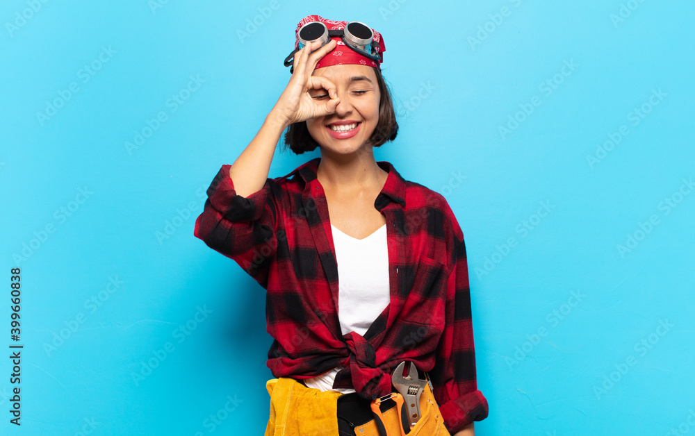 Fototapeta young latin woman smiling happily with funny face, joking and looking through peephole, spying on secrets