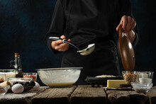 Pastry Chef In Black Uniform Pours Dough Into Waffle Maker Machine For Preparing Sweet Waffle On Rustic Wooden Table With Ingredients On Dark Blue. Frozen Motion. Dessert From Recipe Book.