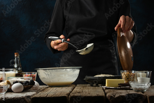 Fotografia Pastry chef in black uniform pours dough into waffle maker machine for preparing sweet waffle on rustic wooden table with ingredients on dark blue