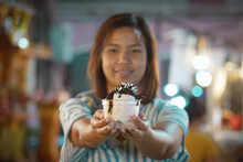 Asian Woman Holding Delicious Ice Cream Dessert In A Cup In Night Market. Thai Famous Gourmet Street Dessert Food. Street Food In Thailand.