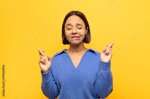 Cuadros en Lienzo young latin woman smiling and anxiously crossing both fingers, feeling worried a