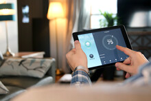 Man Is Adjusting A Temperature Using A Tablet With Smart Home App In Modern Living Room