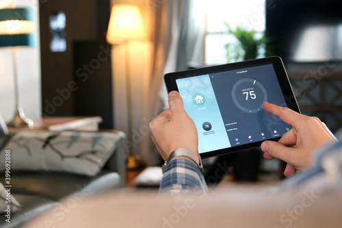 Fototapeta Man is Adjusting a temperature using a tablet with smart home app in modern living room obraz