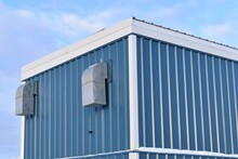 Blue, Silver And White Building With Silver Ductwork Against Blue Sky.  Interesting Abstract Shapes.