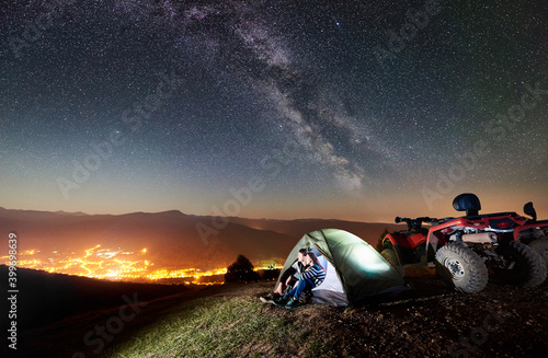 Obraz Happy couple man and woman tourists sitting in tourist tent on the top of mountain with atv quad motorbike, enjoying beautiful view of night sky full of stars, Milky way, luminous city on background - fototapety do salonu
