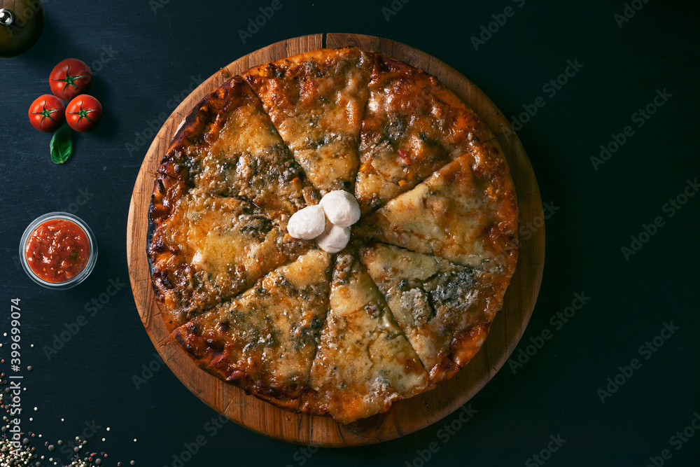 Fototapeta top view Traditional crispy Italian four cheese pizza on a rustic black wood background. Top view of hot pizza.