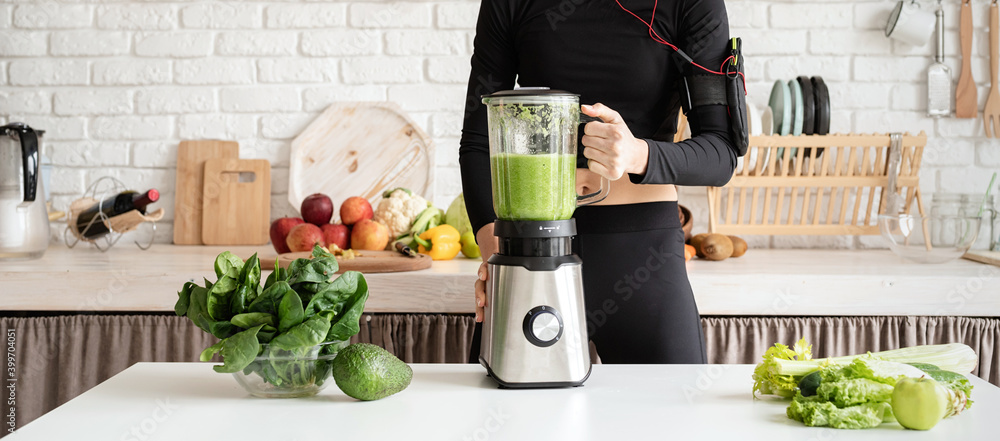 Fototapeta Young blond smiling woman making green smoothie at home kitchen