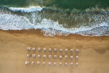 Aerial View Over An Empty Beautiful Sandy Beach With Straw Sunshades And Sunbeds Near Picturesque Sea Waves, Black Sea Coast, Bulgaria.