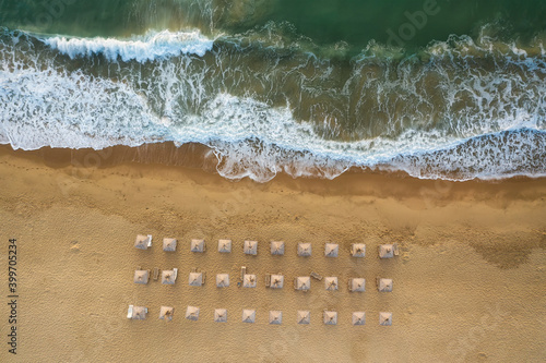 Fotografie, Tablou Aerial view over an empty beautiful sandy beach with straw sunshades and sunbeds near picturesque sea waves, Black Sea coast, Bulgaria