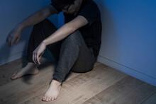 暗い部屋で床に座っている男性