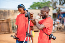 Image Of African Guy, With Camera And A Colleague At Background Bit Blurred - Film Production Concept