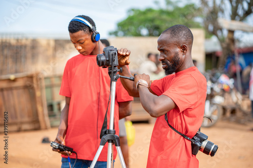 image of african guy, with camera and a colleague at background bit blurred - fi Fotobehang