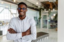 Afro American Young Man In Eyeglasses And Earphones Standing Indoors