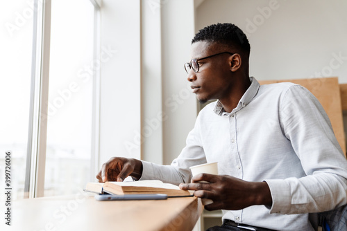 Fotografie, Obraz Afro american focused man reading book and drinking coffee