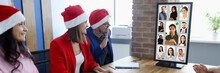 Group Of People Are Sitting At Wooden Table In Santa Hats And Video Communication With Partners. Remote Work During COVID19 Pandemic Concept