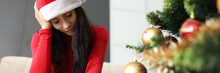 Woman In Santa Claus Hat Touching Glass Of Water And Effervescent Tablet And Holding Her Head Near Tree. Spoiled New Year Holidays Concept