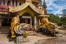 Two Sculptures Of Tigers At The Entrance To A Buddhist Temple. Tigers Are Yellow With Black Stripes With Flowers On Their Teeth.