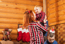 Merry Christmas And Happy Holidays. Mom And Two Sons Are Having Fun Preparing For The New Year In A Cozy Wooden House. The Morning Before Christmas. Portrait Of A Loving Family Nearby.