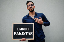 Arab Man Wear Blue Shirt And Eyeglasses Hold Board With Lahore Pakistan Inscription. Largest Cities In Islamic World Concept.
