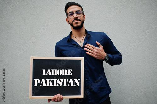 Fotografija Arab man wear blue shirt and eyeglasses hold board with Lahore Pakistan inscription