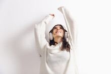 Music. Portrait Of Beautiful Brunette Woman In Comfortable Soft Longsleeve Isolated On White Studio Background. Home Comfort, Emotions, Facial Expression, Winter Mood Concept. Copyspace.