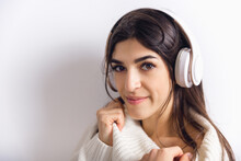 Listening To Music In Headphones. Portrait Of Beautiful Brunette Woman In Comfortable Soft Longsleeve Isolated On White Studio Background. Home Comfort, Emotions, Winter Mood Concept. Copyspace.