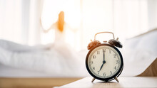 Good Morning New Day. Alarm Clock Wake Up And Woman Standing Open Curtain Window In Bedroom
