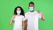 Leinwandbild Motiv Multiracial Couple Pointing Fingers At Masks On Face, Green Background