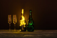 Festive Romantic Postcard. Shining Champagne Wineglasses, Wooden Table On Dark Background. Cozy Still Life Composition Bottles Decorated Garlands. Christmas Valentines Day Holiday Greeting Card.