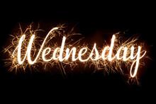 Cursive Word Of 'Wednesday' In Dazzling Sparkler Effect On Dark Background