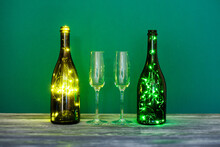 Festive Romantic Postcard. Shining Champagne Wineglasses, Wooden Table On Green Background. Cozy Still Life Composition Bottles Decorated Garlands. Christmas Valentines Day Holiday Greeting Card.