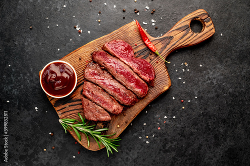 Fotografia Different degrees of roasting beef steak in heart shape with spices on a stone b