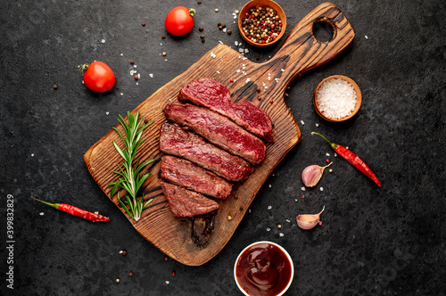 Tela Different degrees of roasting beef steak in heart shape with spices on a stone b