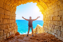 Guy Traveler With Backpack And Raised Up Hands, Holding Camera Stands On Cliff In An Ancient Stone Arch Against The Background Of The Ocean.