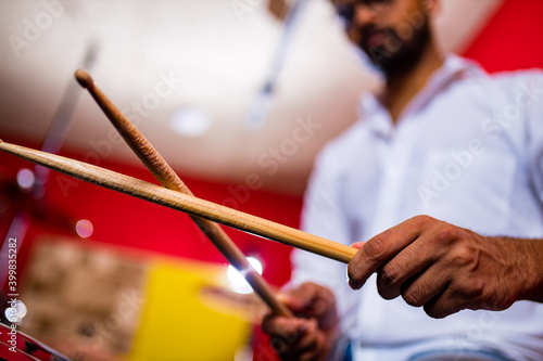 Fotografia, Obraz indian man playing the drums sticks close-up in recording studio